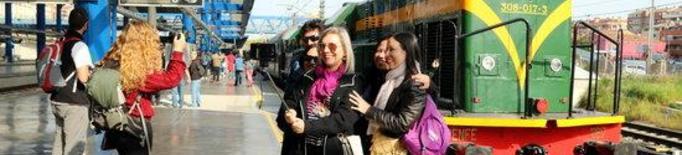 Imatge general d'un grup de passatgers que es fa una 'selfie' davant del tren històric dels Llacs abans de sortir de l'estació de Lleida