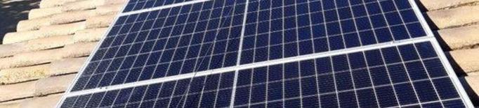 Pla obert d'un operari instal·lant una placa solar a un habitatge de l'EMD de Raimat