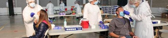 Pla mitjà de dues persones fent-se la PCR aquest divendres 30 d'octubre de 2020 al pavelló de Palafrugell