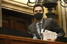 Pla mitjà del president del Parlament, Roger Torrent, accedint a l'hemicicle amb un feix de papers