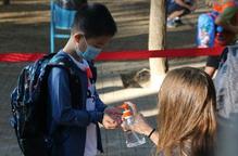 Pla curt d'un alumne de l'Escola Catalònia de Barcelona posant-se gel desinfectant a l'entrada del centre en el primer dia de classes
