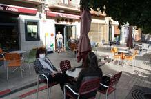 Pla general de diverses persones assegudes en una terrassa de bar del passeig Deu d'Abril de Puigcerdà on es veuen les taules separades