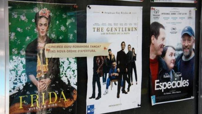 Pla de detall de part de la cartellera de pel·lícules dels Cinemes Guiu de la Seu d'Urgell on es veu un cartell informant que de moment estan tancats
