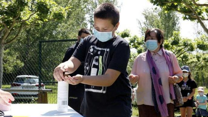 Un nen es renta les mans amb gel hidroalcohòlic abans d'entrar al primer espectacle a l'aire lliure amb públic presencial a Catalunya des del confinament, al Camp de Futbol de Corbins