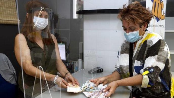 Pla mitjà on es pot veure una clienta canviant 100 euros per 120 molleuros per gastar en botigues de Mollerussa Comercial en el marc de la campanya per injectar diners a les botigues locals per la crisi de la covid-19