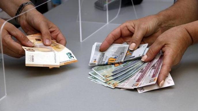 Pla curt on es poden veure molleuros i euros en una operació de canvi en el marc d'una campanya de Mollerussa Comercial per incentivar les compres locals arran de la crisi de la covid-19