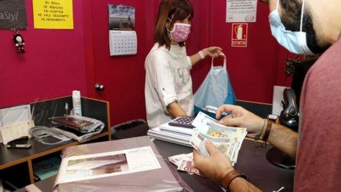 Pla mitjà on es pot veure un client pagant amb molleuros en una botiga de Mollerussa Comercial