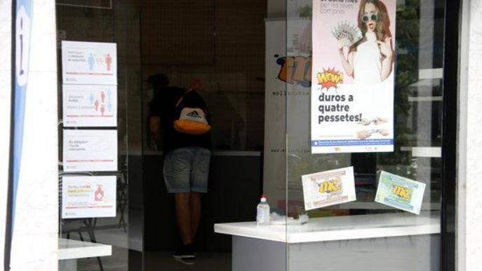 Pla obert on es pot veure el punt d'informació de Mollerussa Comercial amb un cartell de la campanya per incentivar compres arran de la crisi de la covid-19