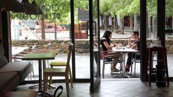Pla de detall d'una part d'una cafeteria de la Seu d'Urgell on es veu una taula buida a l'interior del local i una ocupada a la zona de la terrassa el primer dia de la fase 2 de la desescalada