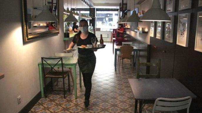 Pla general d'una cambrera d'una cafeteria de la Seu d'Urgell portant una comanda a una de les taules de la terrassa i on es veu que a l'interior del local no n'hi ha cap d'ocupada en aquell momen