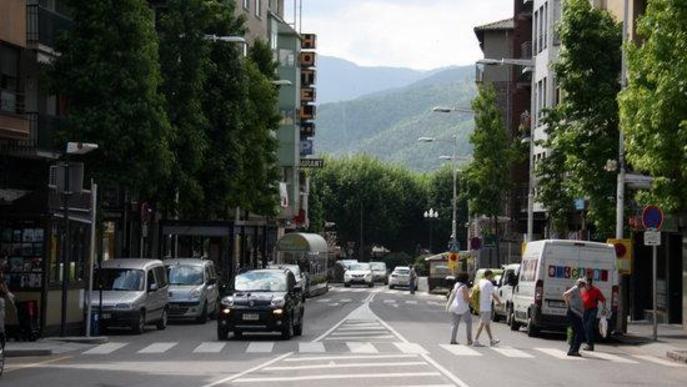 Pla general del carrer Sant Ot, un dels eixos principals de la Seu d'Urgell, on es veuen persones creuant un pas de vianants i circulació de vehicles i un cartell d'un hotel al fons