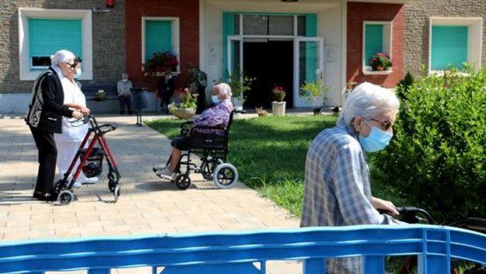 Usuaris de la residència Verge de Ribera de la Pobla de Segur passejant pel jardí del centre