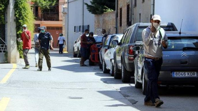 Pla obert on es poden veure diversos temporers amb mascareta en un carrer d'Aitona