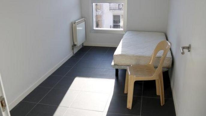 Pla obert d'una habitació individual amb un llit i una cadira en un dels espais que Golmés ha habilitat per aïllar de manera temporal persones amb símptomes de covid-19