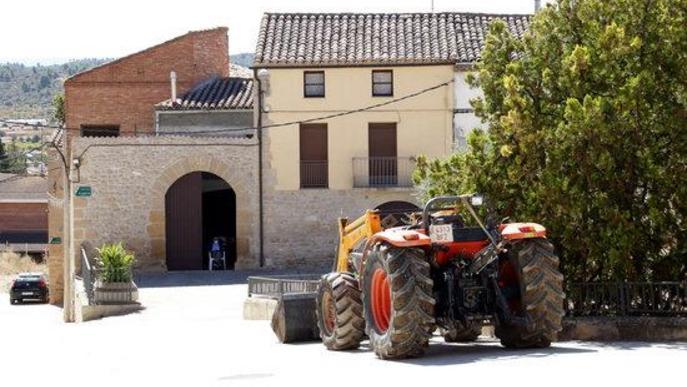 Un veí de Torrebesses assegut a la porta de casa amb el tractor al costat