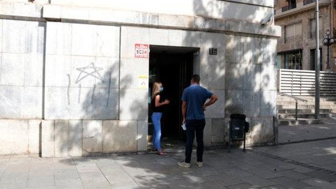 Imatge de dues persones esperant a l'entrada de l'edifici d'Economia de Sant Francesc de la Paeria de Lleida