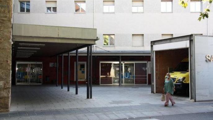 Pla obert on es veu una de les entrades del Sant Hospital de la Seu d'Urgell i una persona passant pel davant amb mascareta