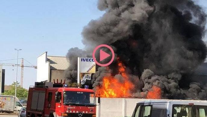 Pla obert on es poden veure les flames de l'incendi en un solar al costat d'un taller a Tàrrega i un camió de Bombers al davant