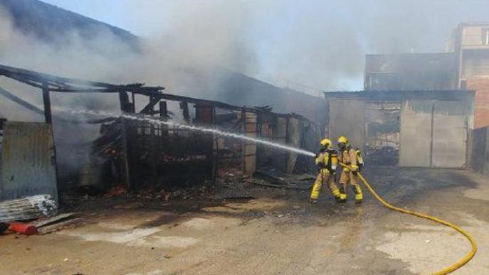 dimecres, 26 agost 2020 16:11 Bombers Pla obert on es pot veure un bomber treballant per controlar el foc en un solar al costat d'un taller a Tàrrega