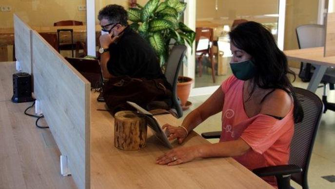 Pla obert d'una part de l'interior de l'espai de 'coworking' de Prullans (Cerdanya) on es veuen dos persones treballant-hi
