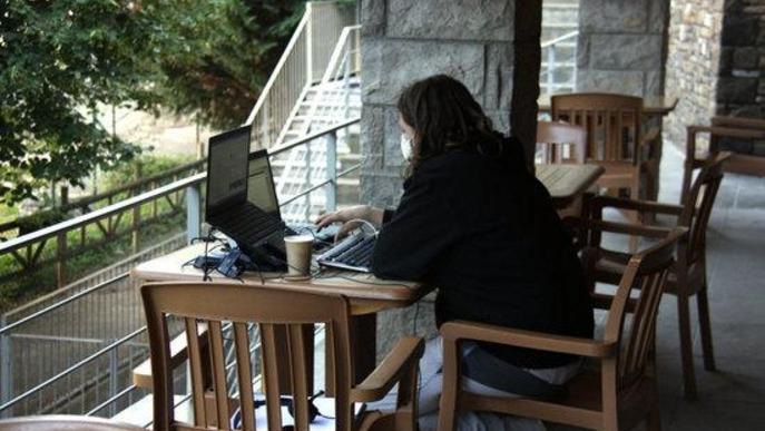 Pla obert de la zona de la terrassa que hi ha al costat de l'espai de 'coworking' de Prullans (Cerdanya) on es veu una persona treballant-hi