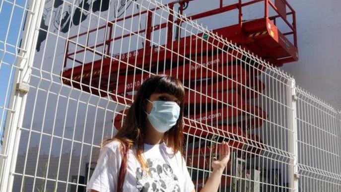 """Pla mitjà de l'artista Cristina Dejuan mostrant el mural """"censurat"""" que havia començat a fer Torrefarrera"""