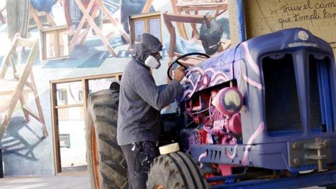 Pla obert de l'artista francès Zeso WF pintant un tractor i al fons part del mural que l'artista Sim Safont a fet a la 5a edició del Gargar