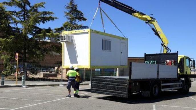 Pla obert on es poden veure dos operaris descarregant una caseta de treball per a l'obra de l'hospital annex a l'Arnau de Vilanova per a casos de covid-19