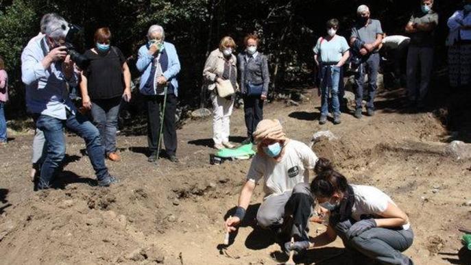 Pla obert de dos arqueòlegs analitzant el què han trobat en l'excavació d'una fossa de la Guerra Civil a Sorpe, a l'Alt Àneu (Pallars Sobirà), i familiars de les víctimes que hi hauria enterrades mirant-ho darrere