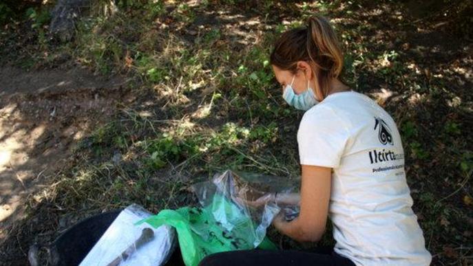 Pla de detall d'una arqueòloga que treballa en l'excavació d'una fossa de la Guerra Civil a Sorpe, a l'Alt Àneu (Pallars Sobirà), guardant part de les restes que s'hi han trobat