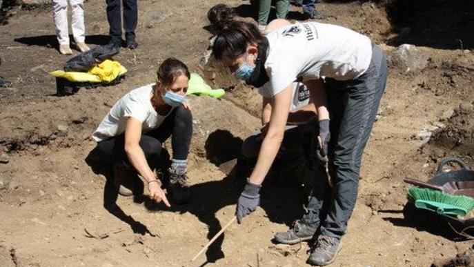 Pla obert on es veuen dues arqueòlogues assenyalant la zona que han de continuar explorant i que forma part en l'excavació d'una fossa de la Guerra Civil a Sorpe, a l'Alt Àneu (Pallars Sobirà)