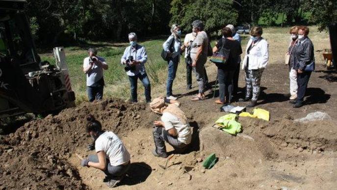 Pla obert de dos arqueòlegs treballant en l'excavació d'una fossa de la Guerra Civil a Sorpe, a l'Alt Àneu (Pallars Sobirà), i familiars de les víctimes que hi hauria enterrades mirant-ho al seu costat