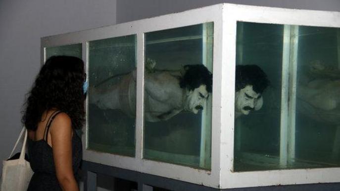 Pla mitjà on es pot veure una noia observant la peça 'Shark' amb la figura de Sadam Husein, de la mostra 'Censored' de Tatxo Benet, a la Panera de Lleida,