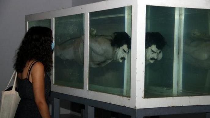 Pla mitjà on es pot veure una noia observant la peça 'Shark' amb la figura de Sadam Husein, de la mostra 'Censored' de Tatxo Benet