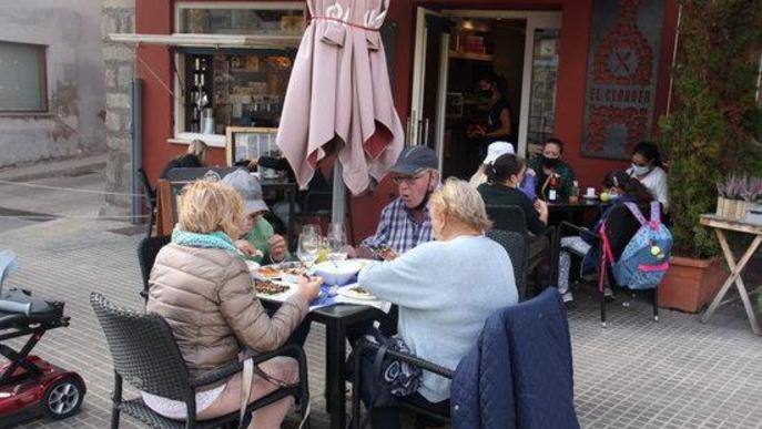 Pla obert on es veuen diverses persones a les taules d'una terrassa de bar de la plaça de Santa Maria de Puigcerdà