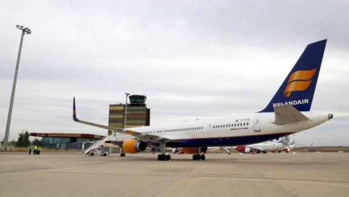 Pla obert d'un avió d'Icelandair, acabat d'aterrar a l'aeroport de Lleida-Alguaire, amb la torre de control al fons