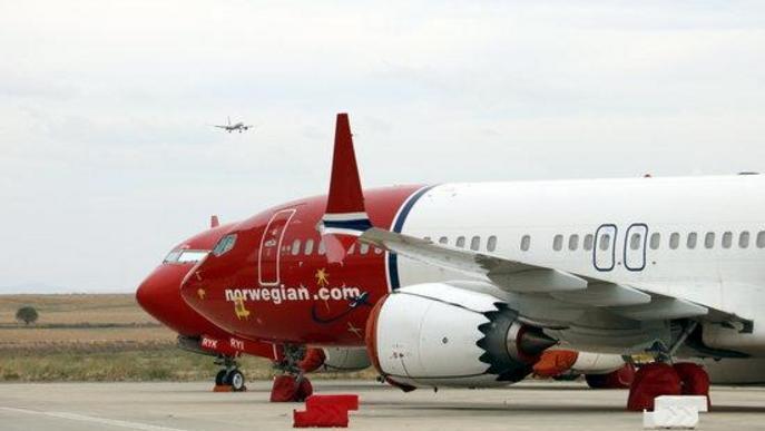 Pla mig d'avions aparcats a l'aeroport de Lleida-Alguaire, amb un avió d'Icelandair aterrant al fons