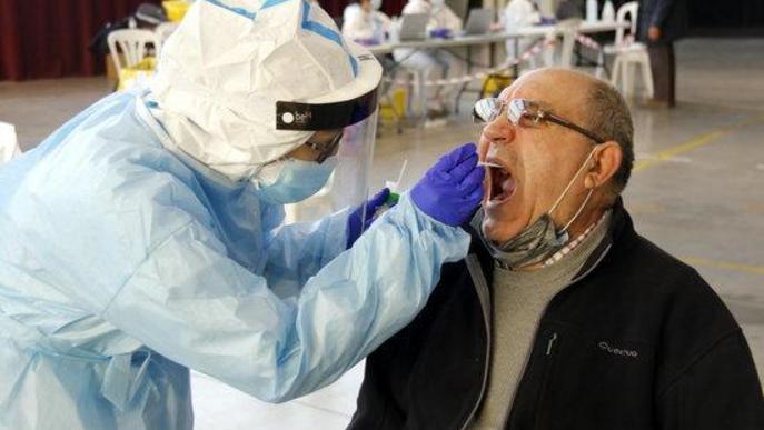 Pla tancat d'un home fent-se la prova PCR amb un tècnic sanitari al pavelló de l'Oli de les Borges Blanques,