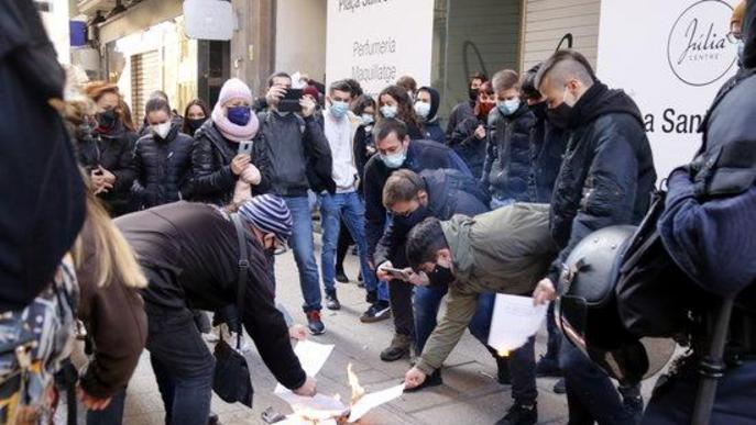 Pla obert de manifestants antifeixistes cremant papers on s'hi havien imprès alguns dels articles de la constitució