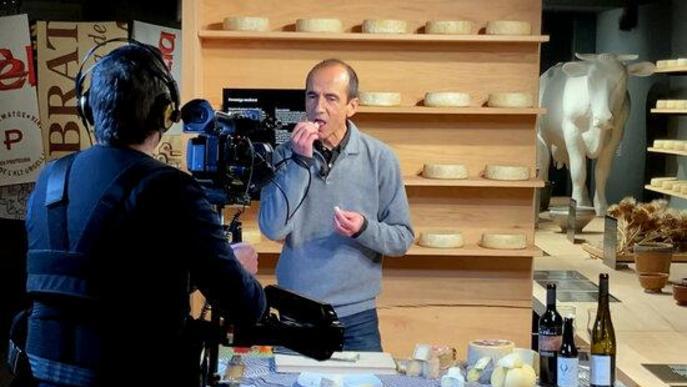 Pla obert del gastrònom Pep Palau tastant un formatge durant la gravació d'un nou vídeo per al canal virtual de la Fira de Sant Ermengol de la Seu d'Urgell i on es veu també el càmera encarregat de l'audiovisual