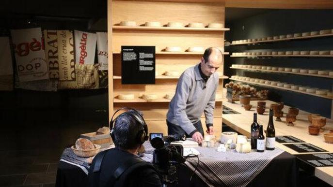 Pla obert del gastrònom Pep Palau durant la gravació d'un nou vídeo de tast de formatges per al canal virtual de la Fira de Sant Ermengol de la Seu d'Urgell i on es veu també el càmera encarregat de l'audiovisual
