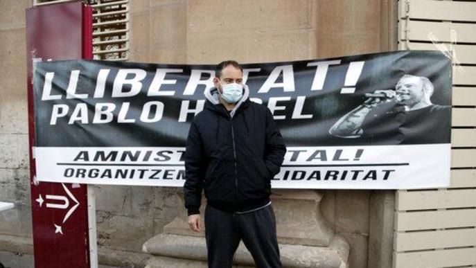 Pla obert on es pot veure al raper Pablo Hasél al davant d'una pancarta que demana la seva llibertat