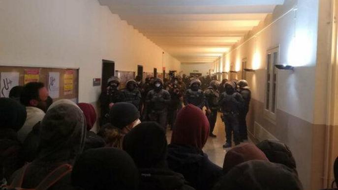Estudiants que donen suport a Pablo Hasél davant d'una línia d'agents antiavalots dels Mossos d'Esquadra per impedir la detenció del raper al rectorat de la Universitat de Lleida