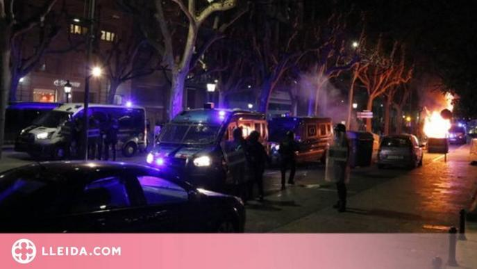Pla obert de furgonetes dels Mossos d'Esquadra i agents a la Rambla Ferran de Lleida, amb un contenidor cremant al fons