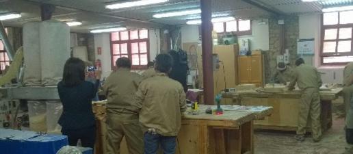 Persones sense llar participen en un taller de mobles